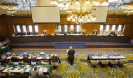 Photograph: Hearing in session, July 2015, Peace Palace, The Hague. Clockwise from top left: Registrar and PCA Senior Legal Counsel Judith Levine; Judge Stanislaw Pawlak; Professor Alfred H. A. Soons; Judge Thomas A. Mensah (Presiding Arbitrator); Judge Jean-Pierre Cot; Judge Rüdiger Wolfrum; PCA Senior Legal Counsel Garth Schofield; former Secretary for Foreign Affairs of the Philippines, Mr. Albert F. Del Rosario; former Solicitor General Mr. Florin T. Hilbay, Counsel for the Philippines; Mr. Paul S. Reichler; Professor Philippe Sands; Professor Bernard H. Oxman; Professor Alan E. Boyle; Mr. Lawrence H. Martin.